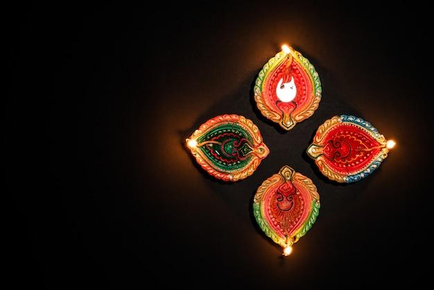 Глиняные дия лампы, зажженные во время празднования дипавали на черном фоне