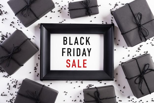 Черная пятница продажа текст на белой рамке с черной подарочной коробке