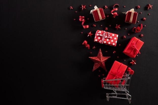 ショッピングカートは、黒の背景にクリスマスの装飾をはねかけます。