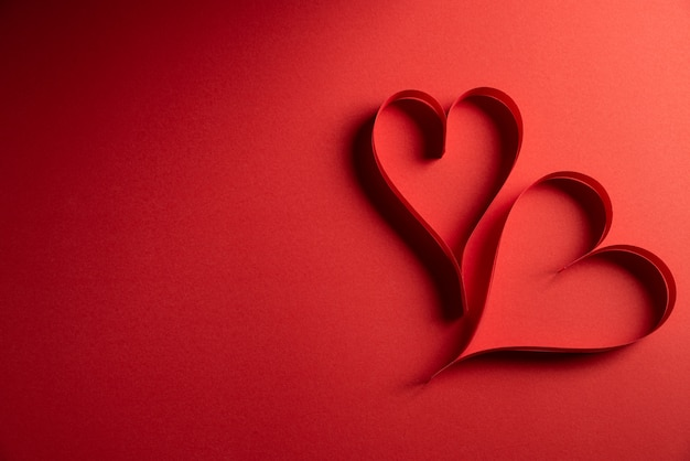 Два красных бумажных сердца на красной бумаге