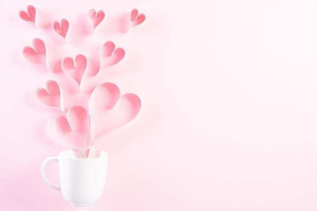 ピンクの紙の心が白いコーヒーカップからはね