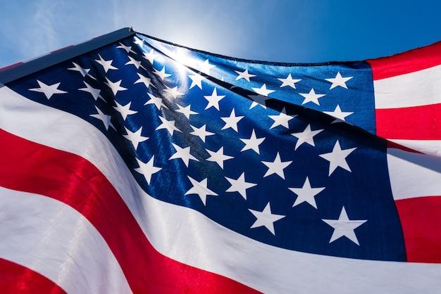 Закройте соединенные штаты америки флаг на фоне голубого неба.