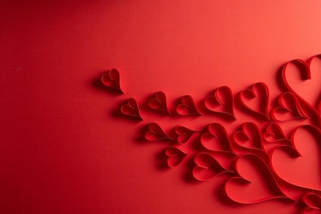 赤い背景の赤い紙の心。愛とバレンタインデーのコンセプト。