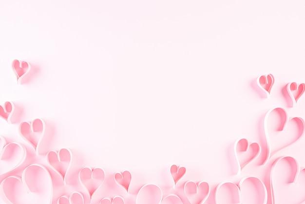 ピンクの紙の背景にピンクの紙の心。愛とバレンタインデーのコンセプト。