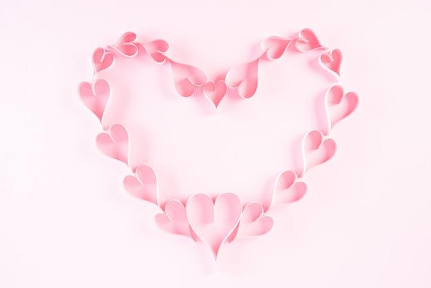 ピンクの背景にハートの形の小さなピンクの紙の心。愛とバレンタインのコンセプト。