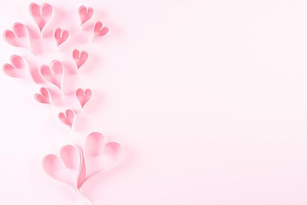 明るいピンクの背景にピンクの紙の心。愛とバレンタインデーのコンセプト。