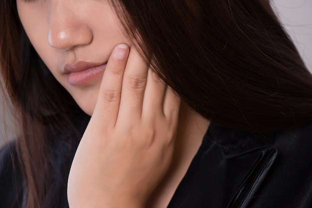 歯痛、虫歯または感受性に苦しむ女性。医療コンセプト。