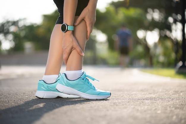Лодыжка вывихнула. молодая женщина страдает от травмы лодыжки во время тренировки