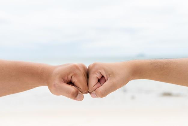 男性の手は一緒にぶつかる。友情の日の概念。