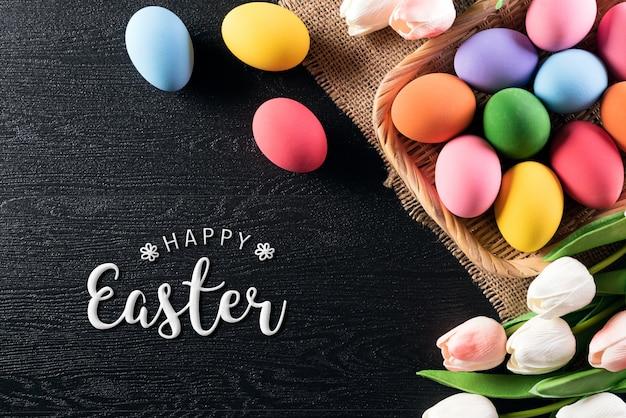 Христос воскрес! разноцветные пасхальные яйца в гнезде с тюльпанами
