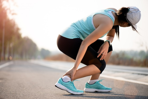 Лодыжка вывихнула. женщина страдает от травмы лодыжки во время тренировки