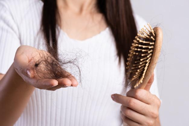 健康的なコンセプト。女性は損傷した長い損失髪と彼女のブラシを表示します