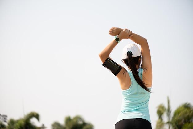 Молодой бегун женщины фитнеса протягивая руку перед бегом в парке.