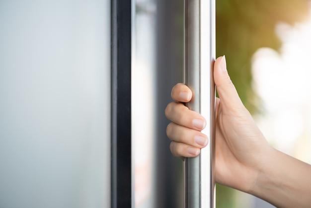 Рука женщины держа дверной бар для того чтобы раскрыть дверь с стеклянной предпосылкой отражения.