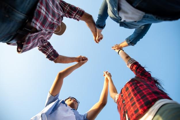 幸せな友人のグループは、一緒に腕を上げ、友情幸福、パートナーシップの概念。