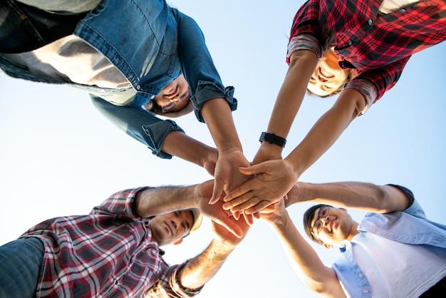 団結とチームワークを示す手のスタックと友達。友情、パートナーシップの概念。