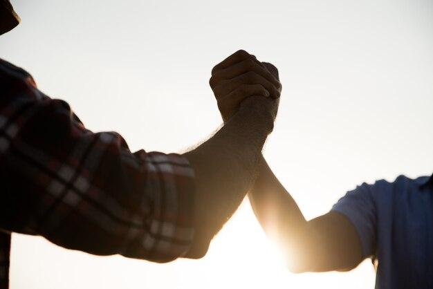 団結とチームワークを示す友好的な握手。友情、パートナーシップの概念。