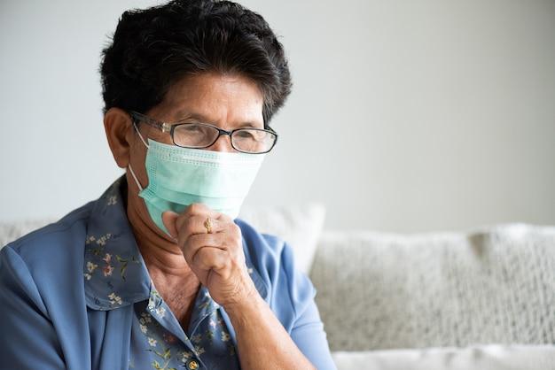 Больная азиатская старуха нося защитную маску