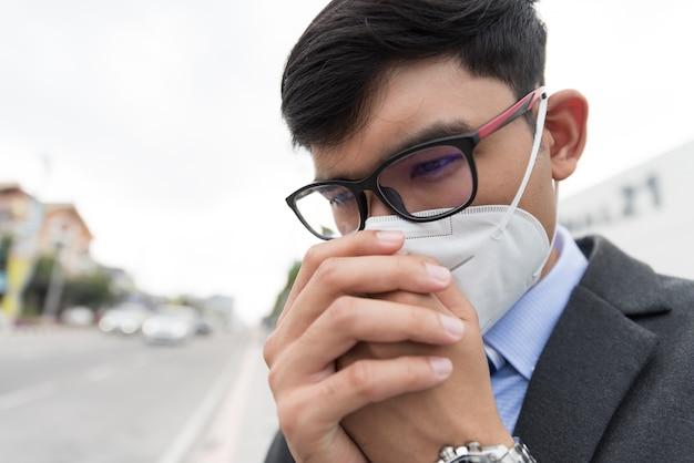 Бизнесмен в костюме носить защитную маску и кашель