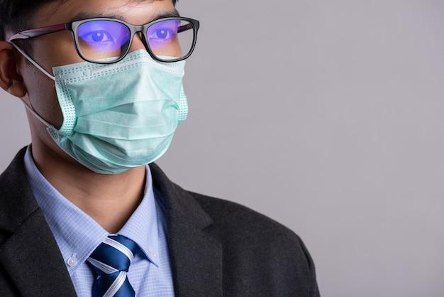 Бизнесмен в костюме носить защитную маску