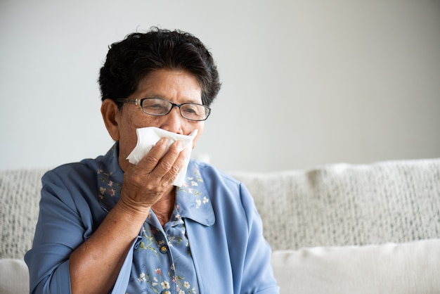 咳しながら口を閉じてティッシュペーパーを使用して病気のアジアの古い女性