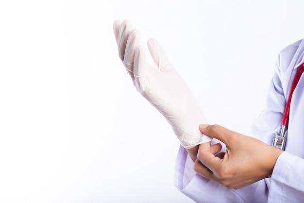 片方の肩に聴診器で女性の医師が滅菌手袋を着用します。