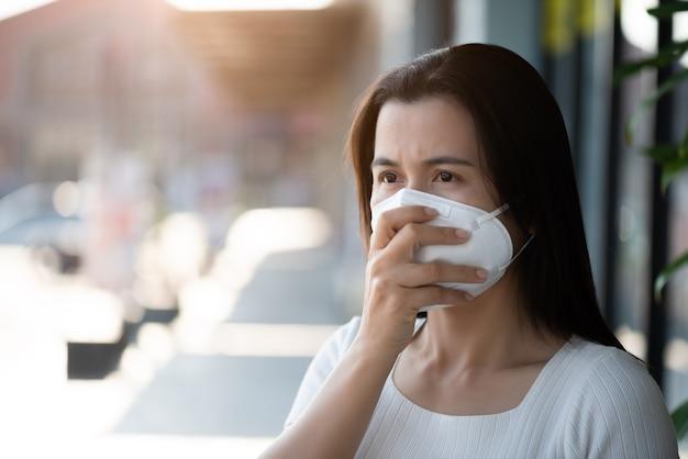 防護マスクと咳をしている女性、コロナウイルスとの戦いの準備をする