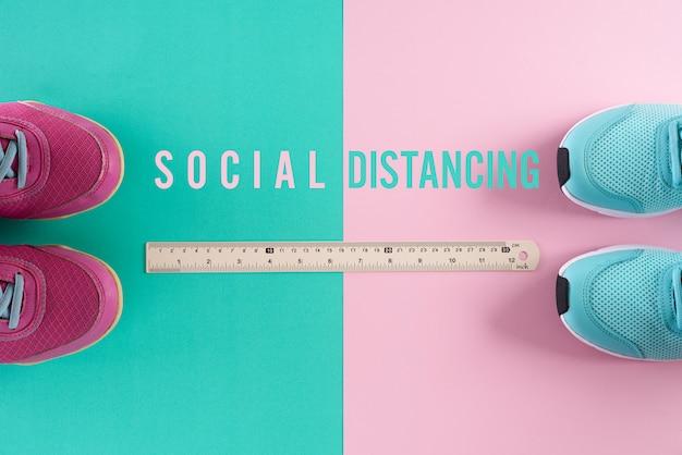 社会的距離の概念。緑ピンクのパステル調の背景に定規が付いている靴