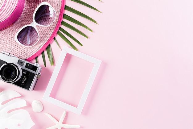 夏の休日の概念のためのピンクのパステル背景にビーチアクセサリー。