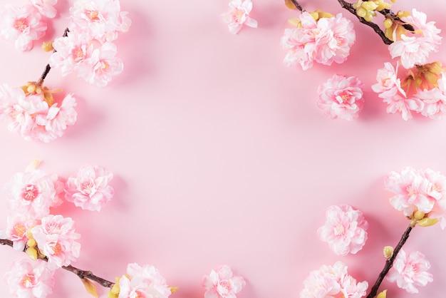 桜の花のパステルピンク色の背景はフラットレイアウトパターンです。