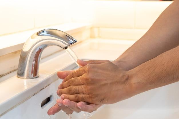 浴室の水で蛇口の下で石鹸で手を洗う男。