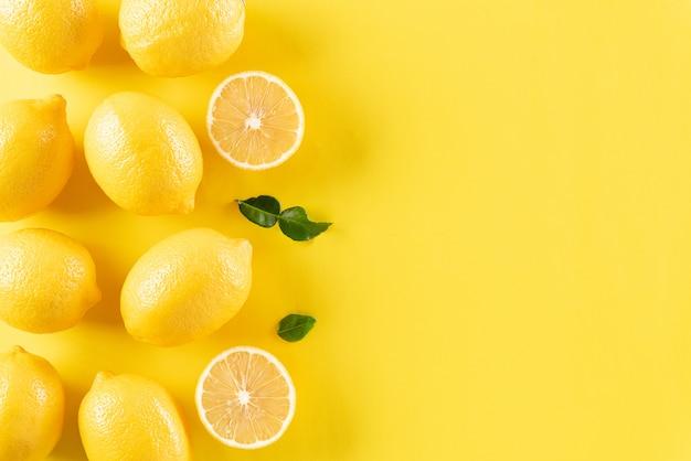 パステルイエローの紙、コピースペースにオレンジ、レモン、緑の葉。
