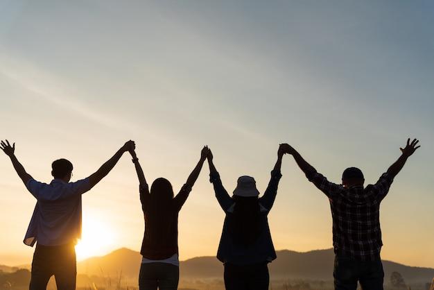 幸せな友人のグループが腕を上げて一緒に楽しんでいます。