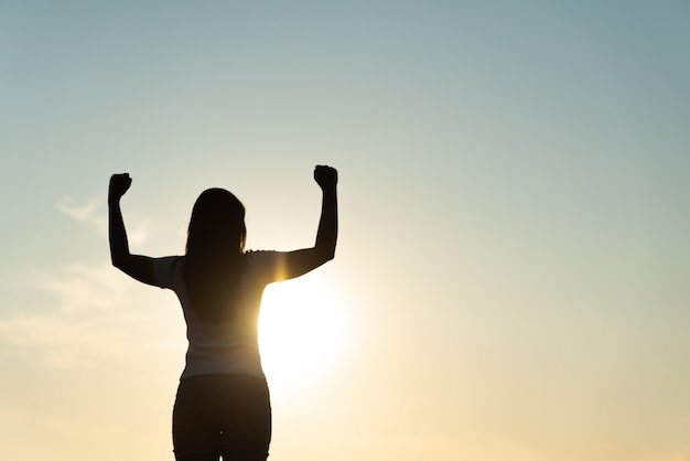 日没時に空気中の拳を持つ女性