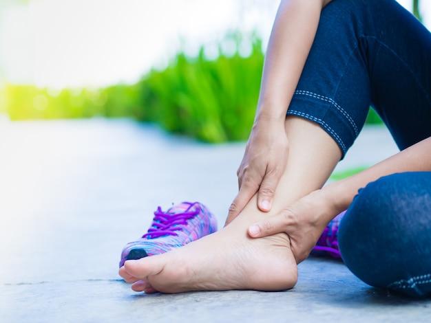 若い女性は運動中に足首の怪我に苦しんで実行しています。