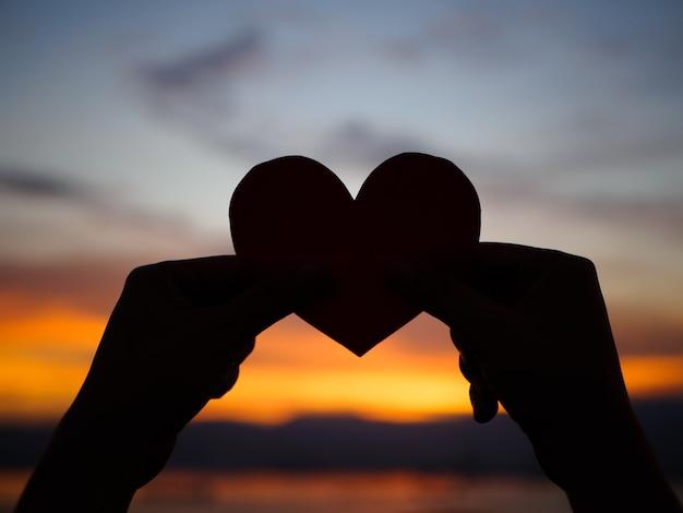 日没の間にシルエットの手が赤い紙の心を上げています