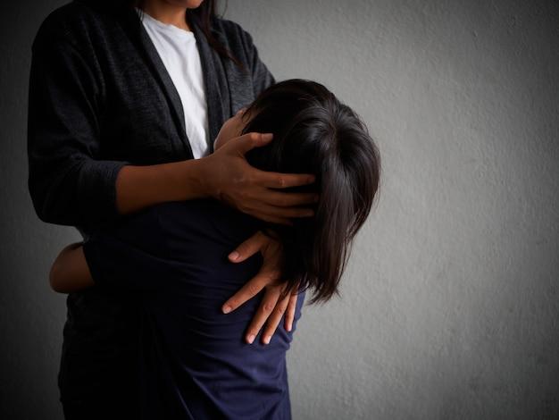 母親が自宅で抱き合っている悲しい息子