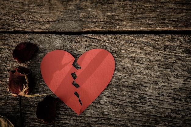 Сушеная красная роза с красной бумагой в виде разбитого сердца на деревянном фоне