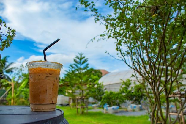 庭の木製テーブルのアイスコーヒー。