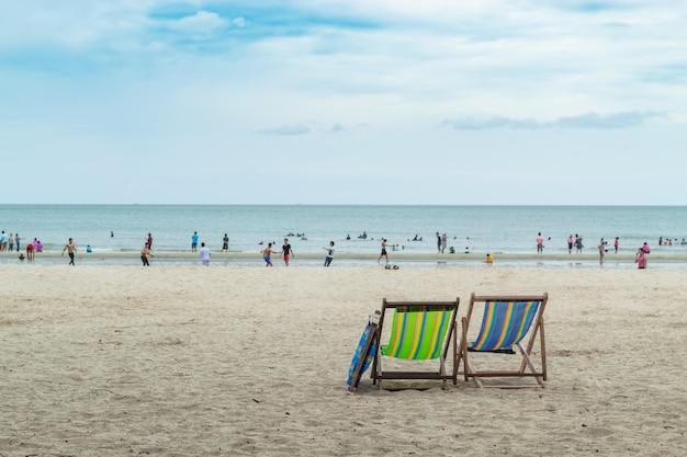 ビーチの椅子とぼやけた観光客。