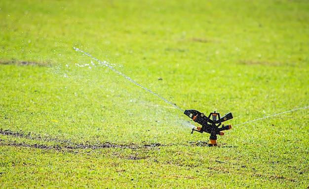 スプリンクラープラスチックは水をまき、緑の芝生です。