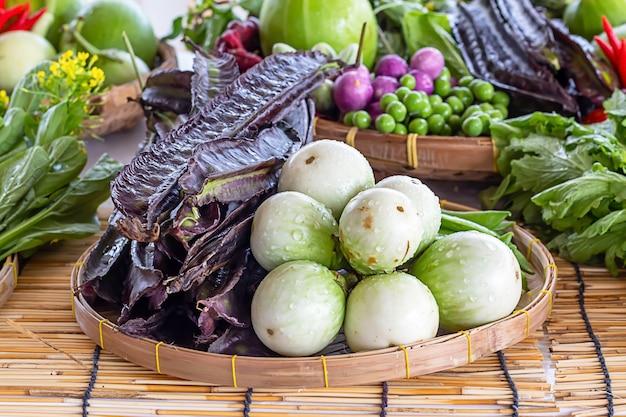 茄子と紫の翼のある豆、竹かごの中の野菜。