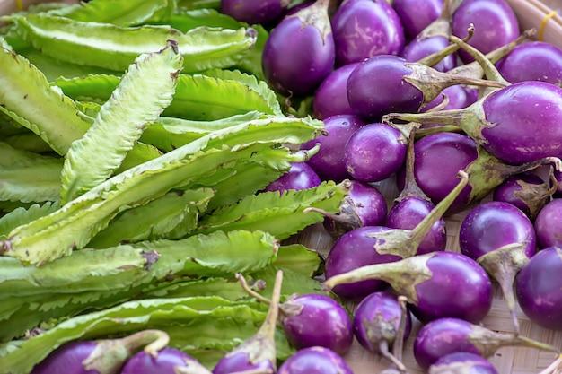 紫色のナスと翼のある豆、竹かごの中の野菜。