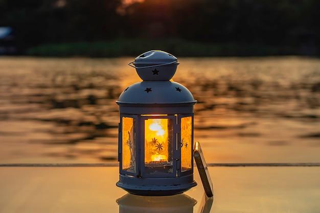 テーブルの上のランプと携帯電話を通して水を反射する太陽の光。