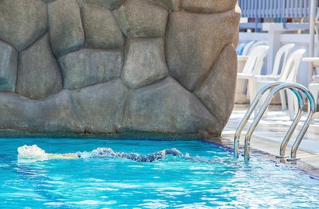 Азиатский мальчик держа заплывание пены в бассейне.