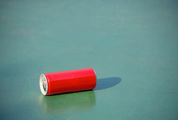緑のコンクリートの床に赤の缶詰飲料