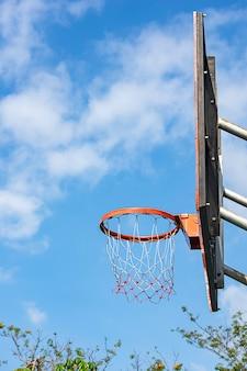 バスケットボールフープ背景ぼやけて木と空。