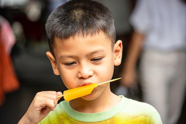 アジアの少年は手でアイスクリームオレンジ味を食べる。