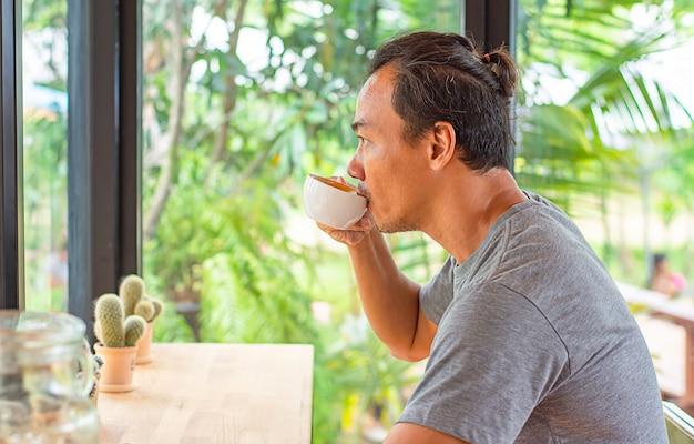コーヒーカップを手で押しながら飲むアジア人
