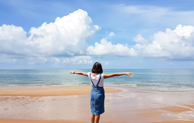 女性はビーチの背景に腕を上げる
